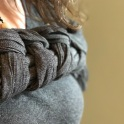 Close up of a plaited finish using a Meh Dai Carrier on the chest of a white woman